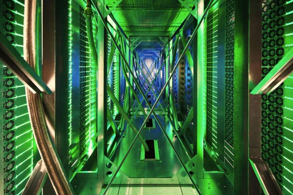 Mayes County, Oklahoma, US: Hundreds of fans funnel hot air from server racks into a cooling unit to be recirculated. The green lights are the server status LEDs reflecting from the front of servers. (photo credit: Google)
